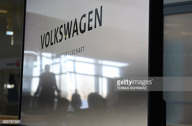 The shadow of a journalist is reflected on a window of the news conference room of German carmaker Volkswagen in Wolfsburg on December 10 2015...