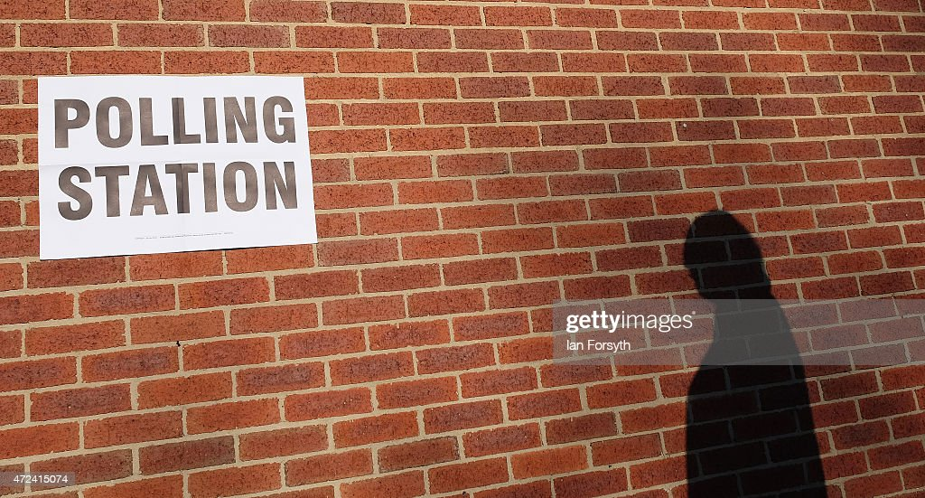 The shadow of a man going to vote is cast on a wall outside a polling centre in a bowling club on May 7, 2015 in Redcar, England. The nation goes to the polls today to vote on what is said to be one of the closest General Elections in decades.