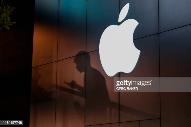 The shadow of a man is cast on the wall of an Apple store as he uses his mobile phone in Beijing on August 26, 2019. - There were signs of a thaw in...
