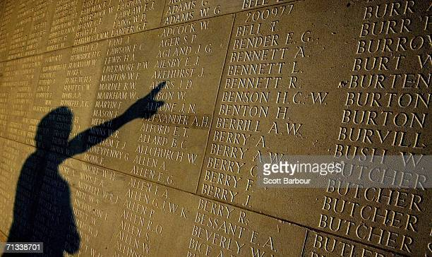 The shadow of a man is cast upon the over 72000 names of soldiers killed in the Battle of Somme at the Thiepval Memorial and AngloFrench cemetery as...