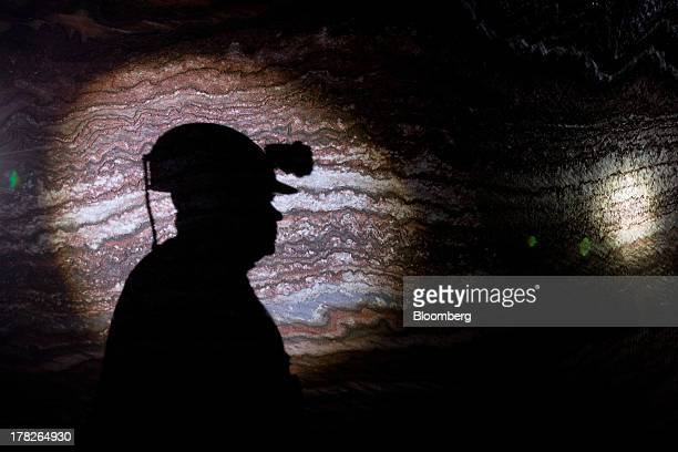 The shadow of a miner falls on the rock wall of a tunnel inside the potash mine operated by OAO Uralkali in Berezniki Russia on Friday Aug 23 2013...
