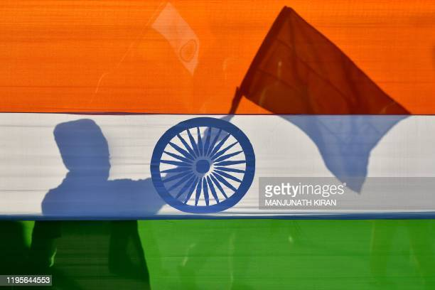 The shadow of a Muslim youth waving the Indian flag is seen on a large Indian flag during a protest rally held by the Muslim community against...