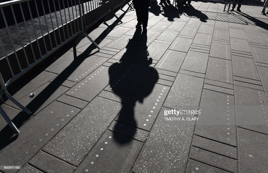 TOPSHOT - The shadow of a NYPD officer as New York Mayor Bill de Blasio makes an announcement during a press conference in Times Square on January 2, 2018 about new barriers to prevent terror attacks and safeguard sidewalks and plazas from vehicles. /