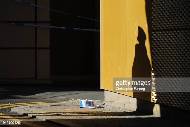 The shadow of a police officer falls on a wall near the scene where a man, aged 20, collapsed after being fatally stabbed last night near Link...