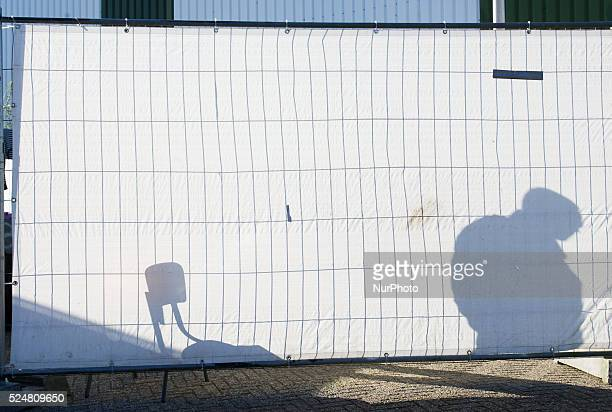 VOORSCHOTEN The shadow of a security guard is seen casted on a fence placed around a sport hall On Friday night three buses with around 125 refugees...