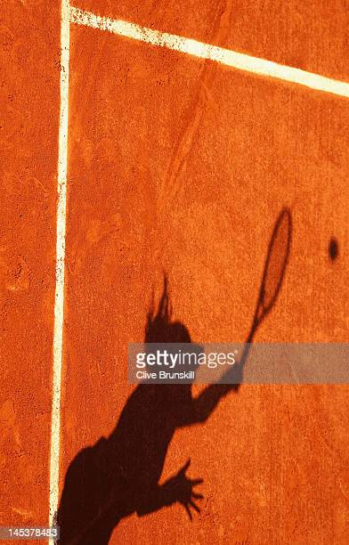 The shadow of a tennis player serving stretches across the clay during the women's singles first round match between Kristina Mladenovic of France...
