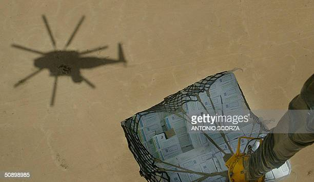 The shadow of a US Marine C853 helicopter is seen below on the desert landscape 26 May 2004 while transporting a pallet with supplies between the...