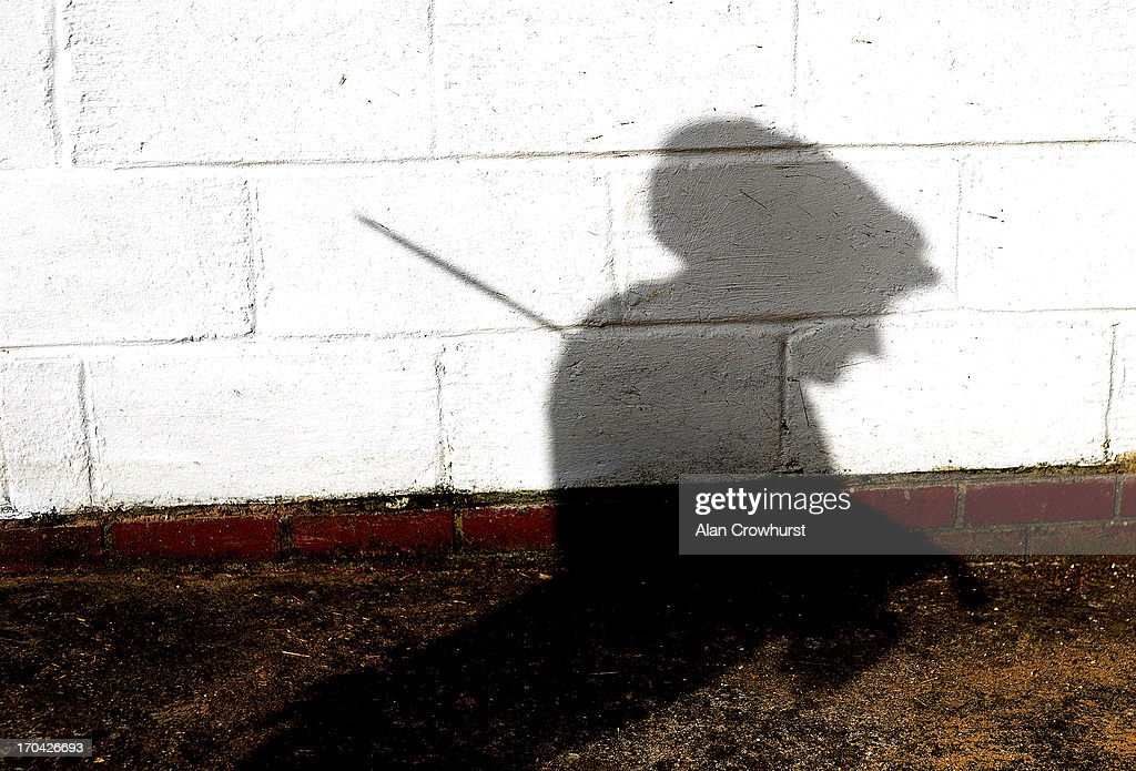 The shadow of a work rider as he awaits his mount on June 13, 2013 in Newmarket, England.