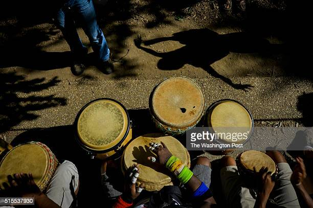WASHINGTON DC JUNE The shadow of Afrika Abney dances to the music of drummers including Hafez Harris bottom center at Meridian Hill Park on Sunday...