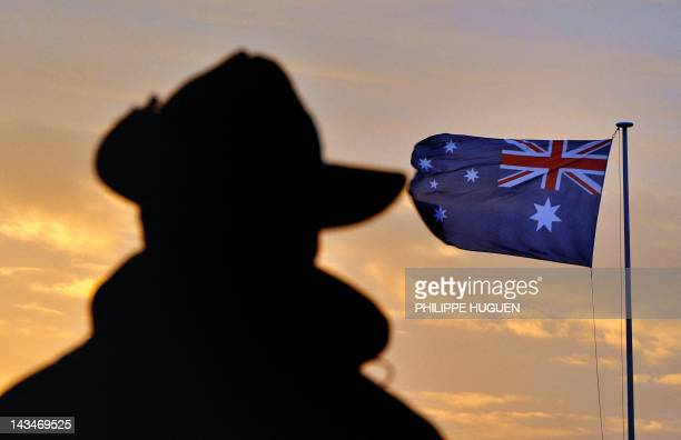 The shadow of an Australian veteran is pictured on April 25 2012 in front of the Australian flag during a dawn service at the Australian War Memorial...