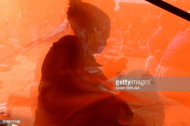 TOPSHOT The shadow of an Indian school student is pictured as people take part in a yoga camp in Hyderabad on June 20 ahead of International Yoga Day...
