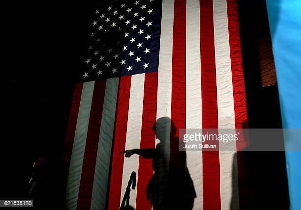 The shadow of Democratic presidential nominee former Secretary of State Hillary Clinton is visible on the American flag during a campaign rally at...