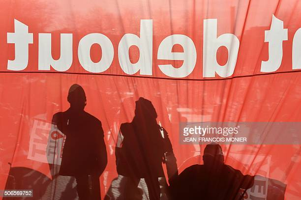 The shadow of demonstrators is pictured through a banner reading 'headwind for employment' on January 24 in Brest northwestern France during a...