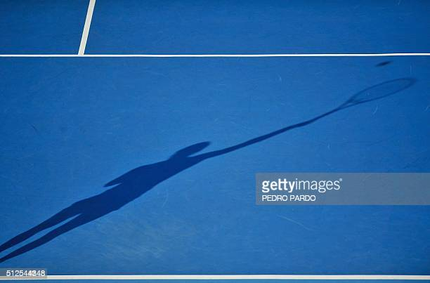 The shadow of Dominika Cibulkova of Slovakia is cast on the court as she serves to Christina McHale of the US during their Mexico Open women's...