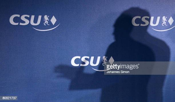 The shadow of Erwin Huber Chairman of the Christian Social Union is seen against a CSU wallpaper during a CSU board meeting on April 4 2008 in...