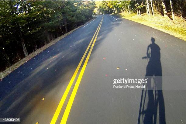 The shadow of Glenn Jordan atop his borrowed hybrid bicycle falls on the Park Loop Road as Jordan nears the end of his journey along the 27mile road...