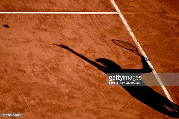 The shadow of Guido Pella of Argentina is cast on the court as he serves to Denis Shapovalov of Canada on day two of the Italian Open at Foro Italico...