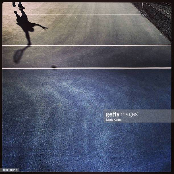 The shadow of Guillermo Garcia-Lopez of Spain is seen as he serves in his first round match against Rajeev Ram of the United States of America during...