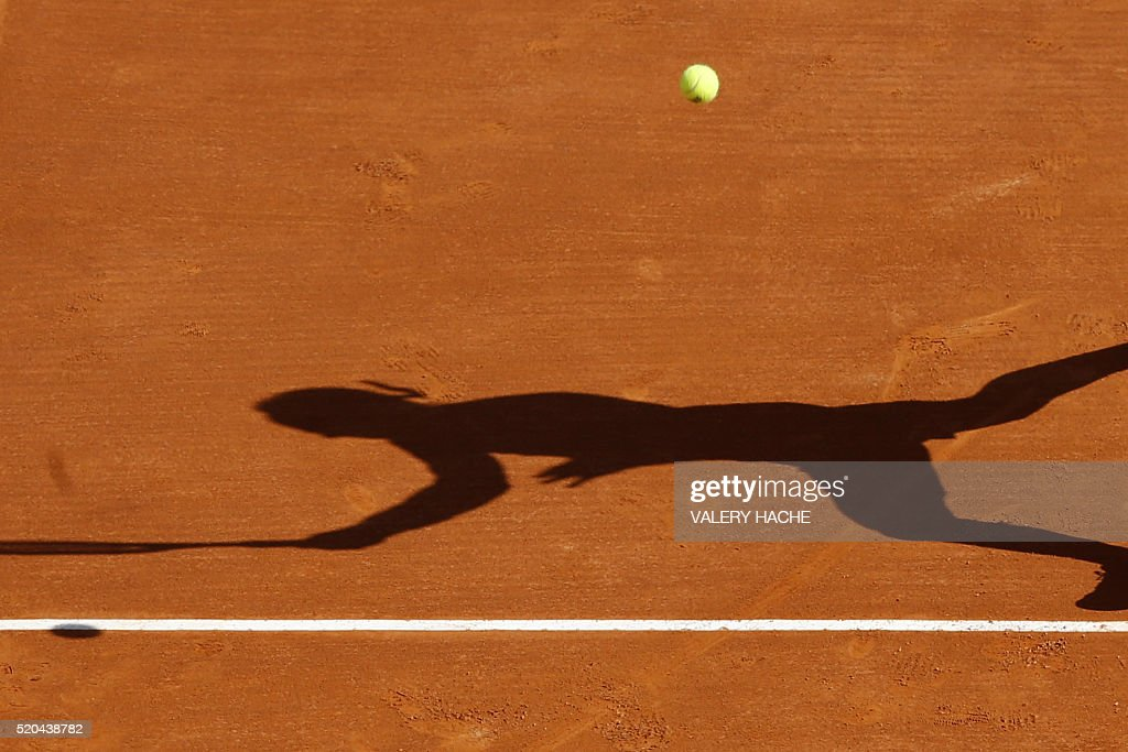 The shadow of Italy's Marco Cecchinato is pictured as he returns the ball to Canada's Milos Raonic during the Monte-Carlo ATP Masters Series Tournament, on April 11, 2016 in Monaco. Raonic won the match 6-3, 7-5.