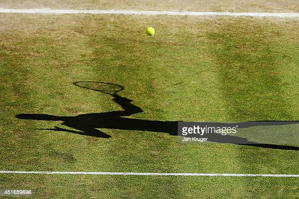 The shadow of Milos Raonic of Canada during the Gentlemen's Singles semifinal match against Roger Federer of Switzerland on day eleven of the...