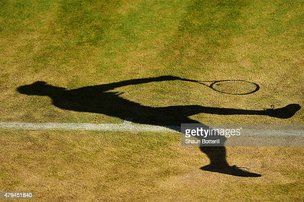 The shadow of Pablo Andujar of Spain serving in his Mens Singles Third Round match against Tomas Berdych of Czech Republic during day six of the...