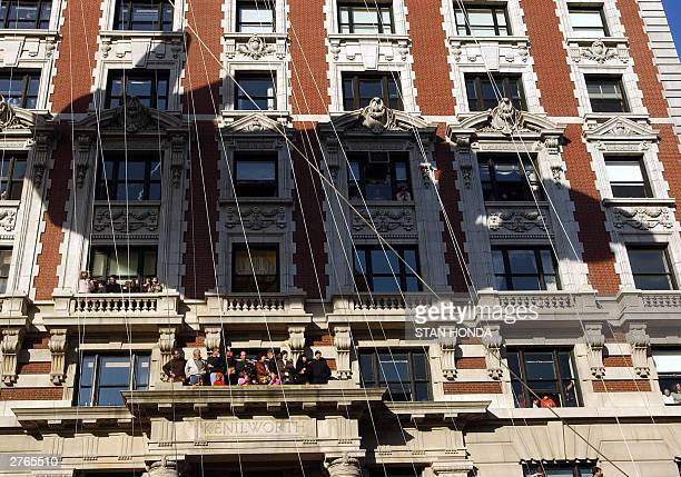 The shadow of Pokemon's Pikachu Balloon falls on an apartment building as spectators watch from balconies and windows during the annual Macy's...