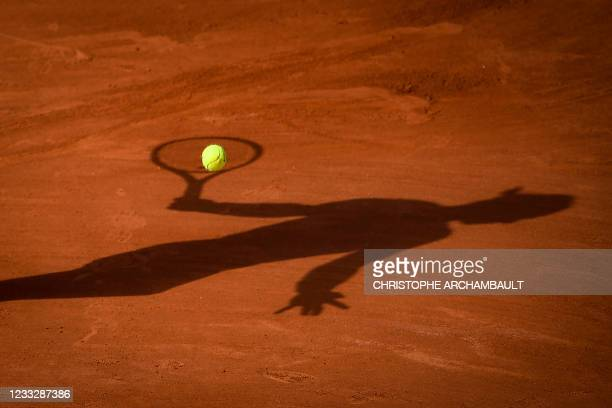 The shadow of Spain's Rafael Nadal is pictured as heA returns the ball to Britain's Cameron Norrie during their men's singles third round tennis...