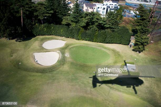 The shadow of the Black Hawk helicopter transporting the the White House Press Corps is seen flying over Kasumigaseki Country Club Golf Course in...