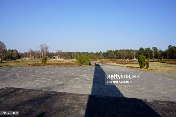 The shadow of the obelisk memorial at the former BergenBelsen German Nazi concentration camp in Lower Saxony Germany 2014 The obelisk was erected by...