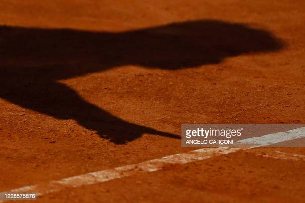 The shadow of the umpire showing a ball mark is cast on the clay during the round 3 match between Britain's Johanna Konta and Spain's Garbine...