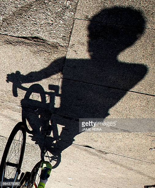 """The shadow of Tinkoff's Spanish cyclist Alberto Contador is projected on the ground before start the fourth stage of the 71st edition of """"La Vuelta""""..."""