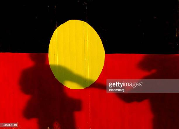 The shadow of two people joining hands is cast on a painted Aboriginal flag on the lawn of Parliament House in Canberra Australia on Wednesday Feb 13...
