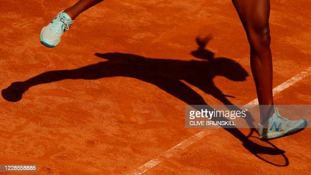 The shadow of USA's Cori Gauff is cast on the clay as she plays a return to Spain's Garbine Muguruza on day four of the Women's Italian Open at Foro...