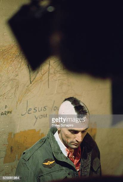 The shadow on a stage light hangs over Robert De Niro as Travis Bickle on the set of Martin Scorsese's Taxi Driver Behind De Niro's head graffiti...