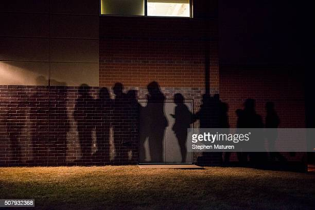 The shadows of caucus goers lined up outside a Democrat Party caucus can be seen on the walls of Maple Grove Elementary in West Des Moines Iowa...