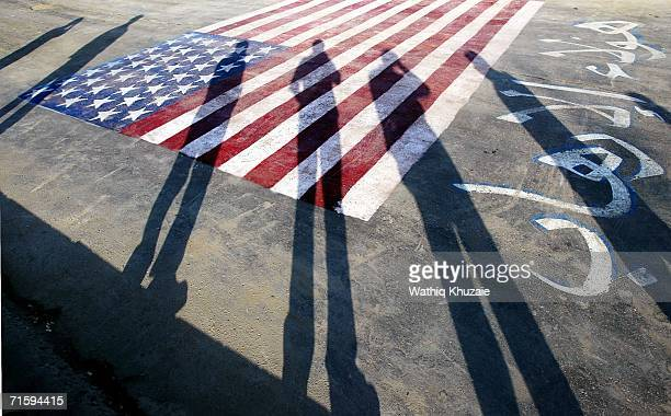 August 5 : The Shadows of Iraqi militiamen of al-Mahdi army, loyal to Shiite cleric Moqtada al-Sadr are cast over an American flag during a parade to...