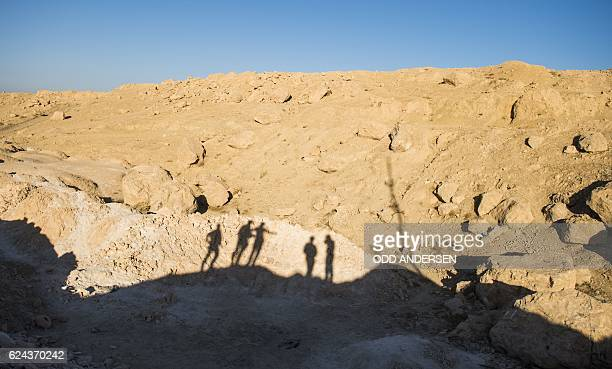 The shadows of members of forces from Iraq's elite Rapid Response Division patrols are seen as they stand at the site of a suspected mass grave on...