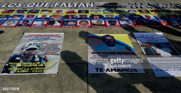 The shadows of people are casted over posters of missing persons during a demonstration in support of victims of the FARC guerrillas during the...