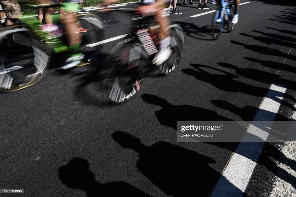 TOPSHOT - The shadows of spectators are cast on the race's route as riders speeds past during the sixth stage of the 105th edition of the Tour de France cycling race between Brest and Mur-de-Bretagne Guerledan, western France, on July 12, 2018.