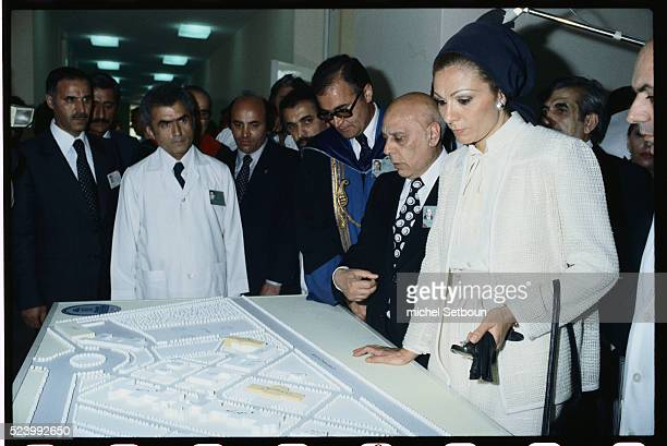 The Shah of Iran and Farah Diba the Empress of Iran look over a diorama while visiting a hospital