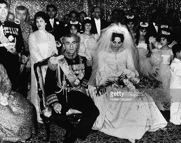 The Shah of Iran sits with his new wife the Empress Farah of Iran The ceremony took place in the Hall of Mirrors with the bride wearing a dress of...