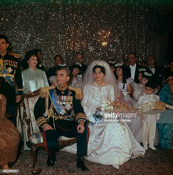 The Shah of Persia and Mohammad Reza Pahlavi and his wife Farah Diba during their wedding the wedding couple are sitting in a hall of the Golestan...