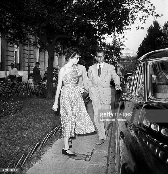 The Shah of Persia Mohammad Reza Pahlavi being about to open the car door for his wife the Princess Soraya Esfandiary Bakhtiari of Iran on via Veneto...