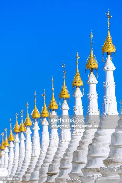 The shape of the white pagoda spires in a row at Sandamuni temple, Mandalay, Myanmar.