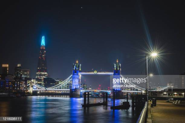 The Shard and Tower Bridge are lit up blue to show appreciation and support for NHS staff during the COVID19 outbreak March 26 2020 in London United...
