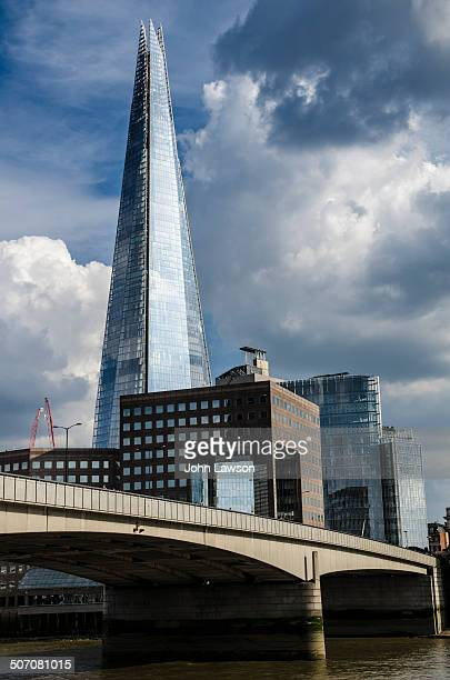 The Shard building in London, England, UK viewed over The River Thames and London Bridge in the foreground. In the middle ground and at the base of...