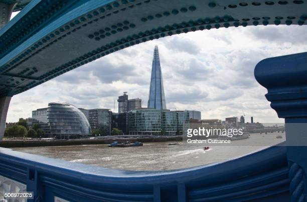 The Shard, framed by the iron structure of Tower Bridge in London, England.
