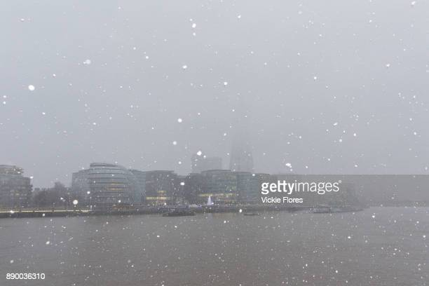 The Shard is seen shrouded in snow clouds in front of the River Thames during a heavy snow shower on December 10th 2017 Much of the UK has been hit...