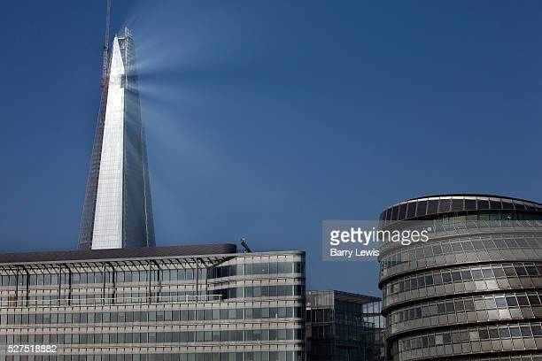 The Shard nearing completion towers over London's City Hall as it reflects the rising sun on a misty morning