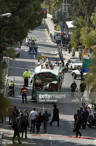 The shattered Israeli passenger bus is towed away under police escort from the scene of a suicide bomb attack January 29 2004 in Jerusalem Israel The...